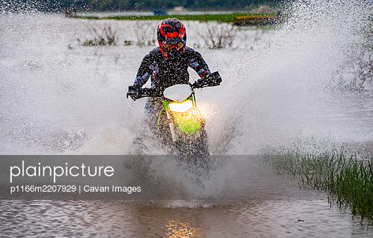 woman riding her dirt-bike through a lake near Pak Chong / Thailand - p1166m2207929 by Cavan Images