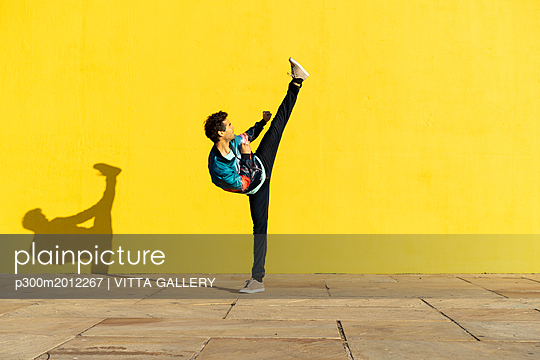 Acrobat doing movement training in front of a yellow wall - p300m2012267 von VITTA GALLERY