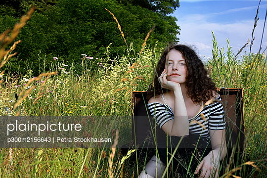 Portrait of young woman sitting in suitcase on a meadow - p300m2156643 by Petra Stockhausen