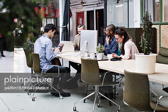 plainpicture - plainpicture p426m1579954 - Business coworkers using te... - plainpicture/Maskot