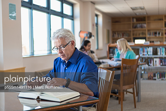 Older man reading book in library and writing notes - p555m1491116 by Marc Romanelli