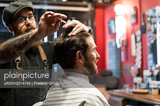Hairdresser cutting man's hair in salon - p623m2214743 by Frederic Cirou