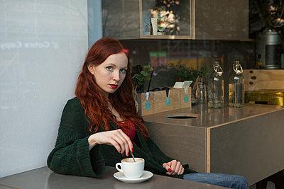 Frau im Cafe guckt durch Fensterscheibe - p045m1208203 von Jasmin Sander