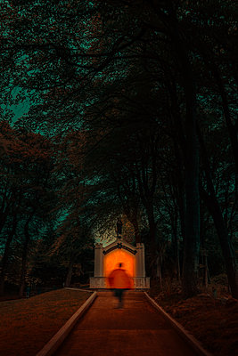 Silhouette against lighted structure in a forest at night - p1681m2283652 by Juan Alfonso Solis