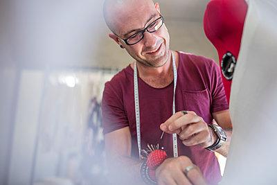 Smiling tailor working on dress in studio - p300m1581448 von zerocreatives