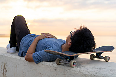 Young Chinese man with skateboard lying on wall at the beach - p300m2012284 von VITTA GALLERY