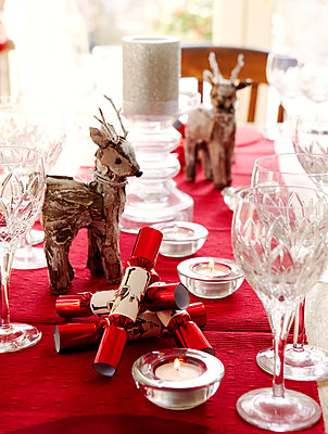 Crystal wineglasses and reindeer figurines on Christmas dining table - p349m790239 by Brent Darby