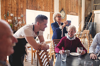 Young waiter leaning on chair while senior friends socializing in restaurant - p426m1506295 by Maskot