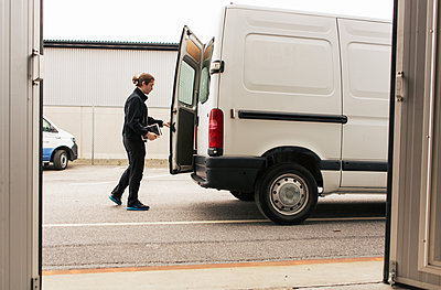 Side view of manual worker closing delivery van while standing on road - p426m1580277 by Kentaroo Tryman