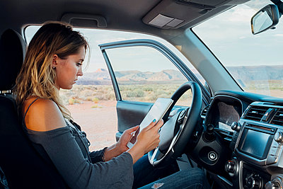 Young woman sitting in vehicle, looking at digital tablet, Mexican Hat, Utah, USA - p924m1580623 by Seth K. Hughes