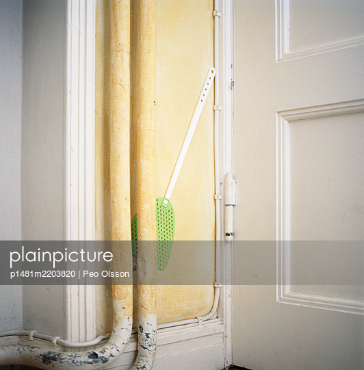 Fly swatter jammed between waterpipe and wall  - p1481m2203820 by Peo Olsson