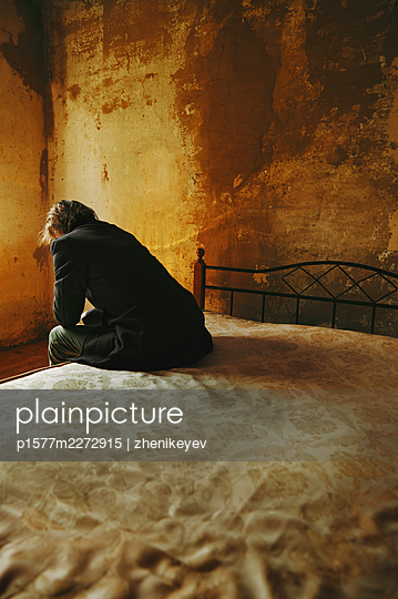 Man sitting on the bed in a dark room - p1577m2272915 by zhenikeyev