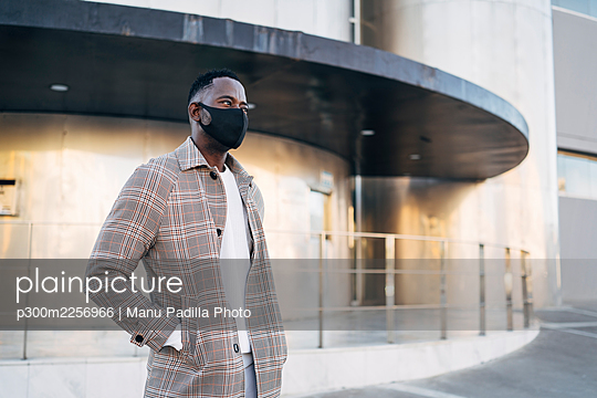 African man wearing protective face mask with hand in pocket standing against building - p300m2256966 by Manu Padilla Photo
