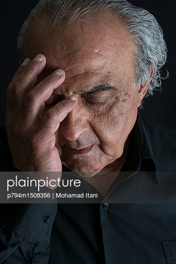 plainpicture | Photo library for authentic images - plainpicture p794m1508356 - Sad elderly man hand on face - plainpicture/Mohamad Itani