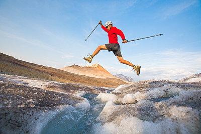 Hiker in mid-air, crossing glacial river. - p1166m2153442 by Cavan Images