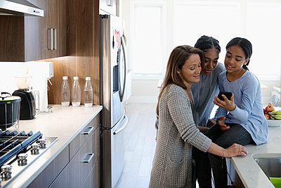 Mother and daughters using smart phone in kitchen - p1192m2094359 by Hero Images
