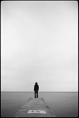 Man standing alone at end of pier - p3720297 by James Godman