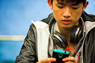Asian man with headphone using cell phone - p555m1411617 by Adam Hester