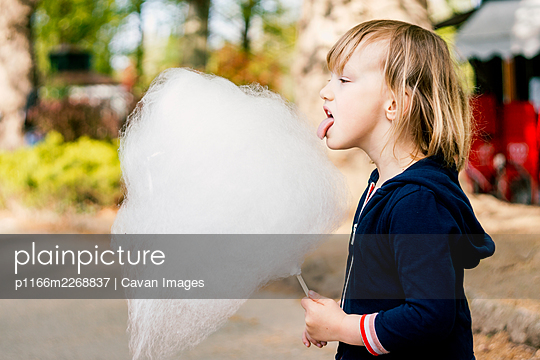 Cute young girl 3-4 years old eating cotton candy - p1166m2268837 by Cavan Images