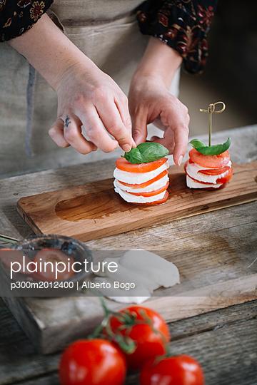 Woman's hands preparing Caprese Salad, partial view - p300m2012400 von Alberto Bogo