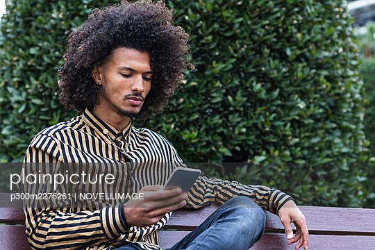 Young man using mobile phone on bench - p300m2276261 by NOVELLIMAGE