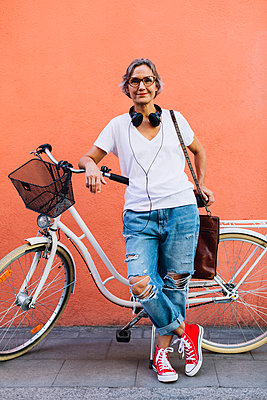 Portrait of confident woman with bicycle standing against wall - p1166m1485573 by Cavan Images