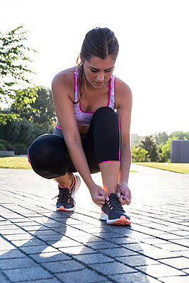 Pretty fit woman tightening sneakers during workout in the park. - p1166m2130098 by Cavan Images