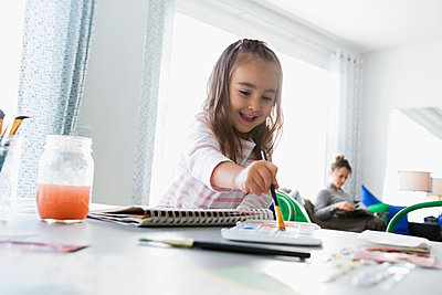 Smiling girl painting at dining room table with mother in background - p1192m1201958 by Hero Images