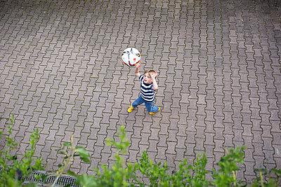 Junge im Hof mit Fußball - p1308m2211642 von felice douglas