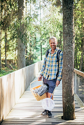 Portrait of smiling man with picnic basket standing on footbridge in forest - p426m2213168 by Maskot