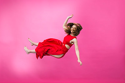 Woman in red dress mid-air - p427m2059719 by Ralf Mohr
