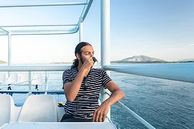 Man drinking coffee on ferry, Corfu, Kerkira, Greece - p429m2075348 by Tamboly