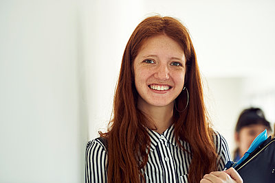 Female student smiling in corridor, portrait - p623m1579549 by Frederic Cirou