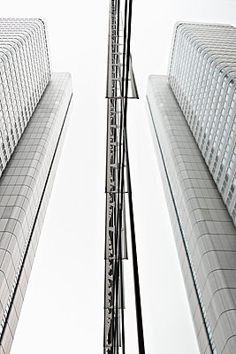 Low angle view of modern office buildings in business district - p92411817f by Oanh