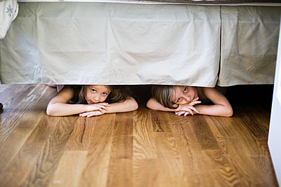 Boy and girl hiding under bed - p924m1404257 by Sasha Gulish
