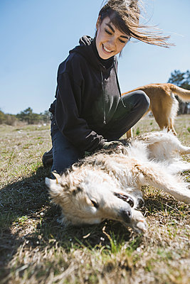 Young woman playing on grass with dog from animal shelter - p1427m2174061 by Oleksii Karamanov