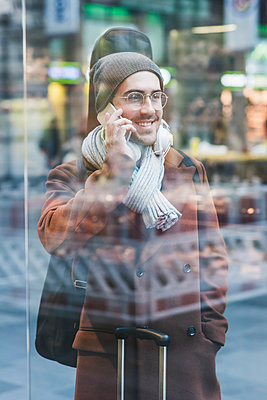 Smiling young man with guitar case on cell phone - p300m1562784 by Uwe Umstätter