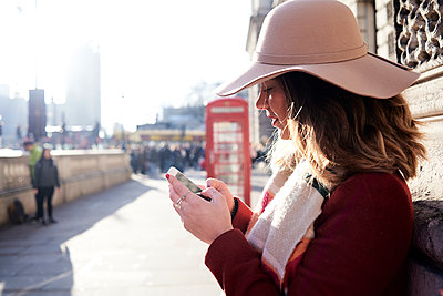 UK, London, woman in the city wearing a floppy hat using cell phone - p300m2103749 by Ivan Gener