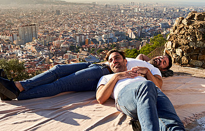 Gay couple lying on observation point against cityscape, Bunkers del Carmel, Barcelona, Spain - p300m2256700 by Veam