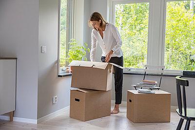 Woman unpacking cardboard box - p352m2119077 by Helena Bonnevier