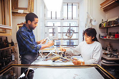 Male and female artists making picture frame at workbench in store - p426m2089064 by Maskot
