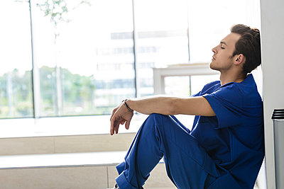 Young male junior doctor sitting on floor in hospital corridor - p429m2097734 by suedhang photography