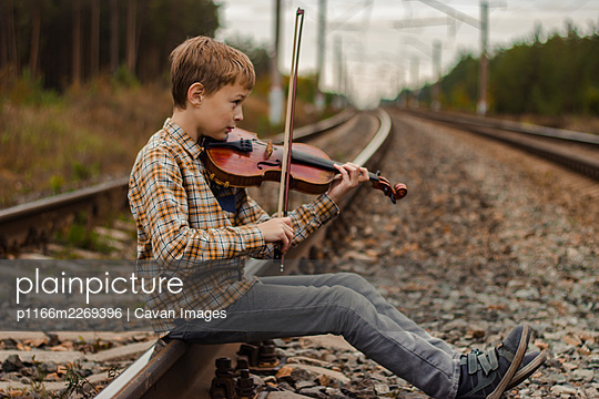 A beautiful blond boy sits on the rails of the railway and plays the v - p1166m2269396 by Cavan Images
