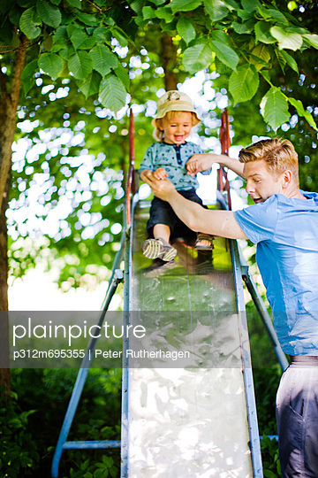 Father holding son on slide - p312m695355 by Peter Rutherhagen