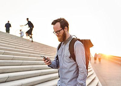 Mann mit Smartphone auf Treppe - p1124m1176675 von Willing-Holtz