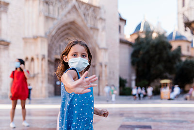 Girl wearing mask standing on street with woman in background - p300m2220683 by Ezequiel Giménez