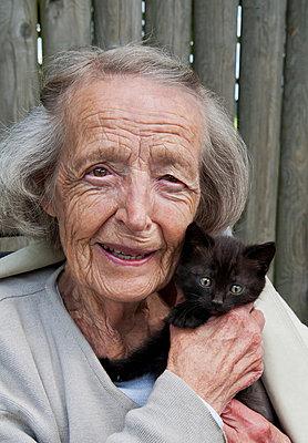 Portrait of 80 plus years woman with black kitten - p4269214f by Håkan Jansson