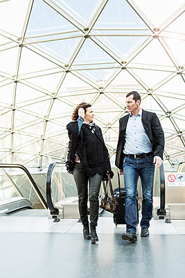 Business people talking while walking in front of escalator at railroad station - p426m1085311f by Kentaroo Tryman