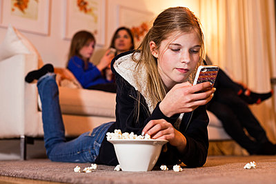 Girl using mobile phone while having popcorn on floor with family in background - p426m803235f by Maskot