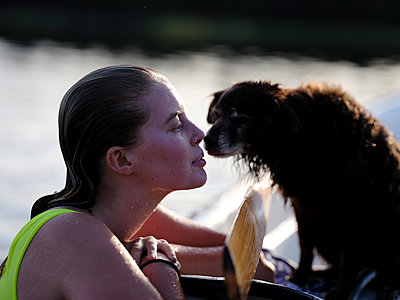 Young woman and dog by the lake - p551m2134149 by Kai Peters